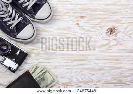still life with sneakers, camera and wallet with dollars