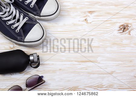still life with sneakers, sunglasses and perfume on wooden background