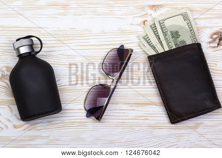 Top view of gentlemanly set: sunglasses, perfume, wallet with money on old wooden background