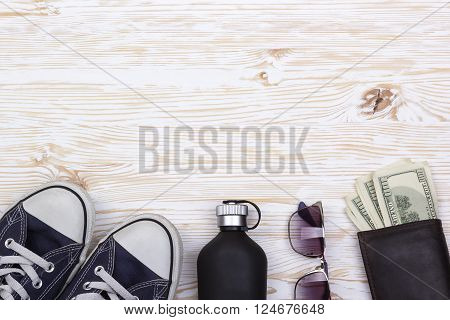 still life with sneakers, sunglasses, wallet with money and perfume on wooden background