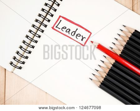 Red pencil standout from black pencil and handwriting word Leader on wood background leadership business concept