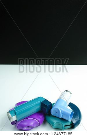 Asthma medication. Set of inhalers and medication for the treatment of bronchial asthma on a black background copy space