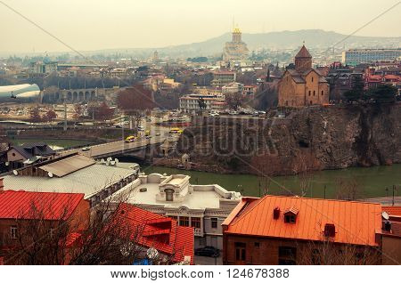 Aerial view of Tbilisi Georgia city center. With Holy Trinity Cathedral at the background and car traffic rainy day. Toning