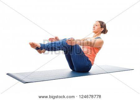 Beautiful sporty fit woman doing Ashtanga Vinyasa yoga asana Paripurna navasana - boat pose beginner variation isolated on white background
