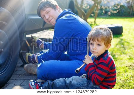 Little blond child of 2 and his father changing wheels on car with pneumatic wrench. Man in uniform teaching his son working with tools.