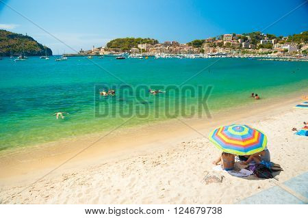 Colorful umbrellas on Puerto de Soller, Port of Mallorca island in balearic islands, Spain. Beautiful picture of people resting on the beach on bright summer day.