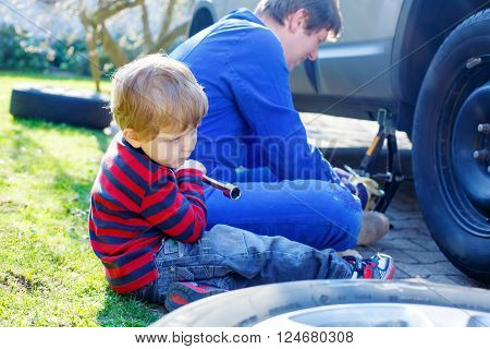 Adorable blond kid boy and his father changing wheels on car with pneumatic wrench. Man in uniform teaching his son working with tools.