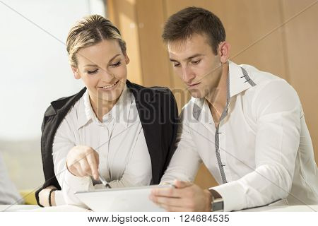Two business colleagues working on a tablet computer in an office