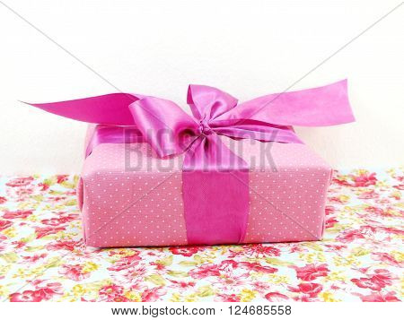 Pink Polka Dot Gif Box With Pink Bow On Printed Fabric