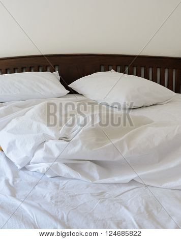 Morning view of an unmade bed in white bedroom