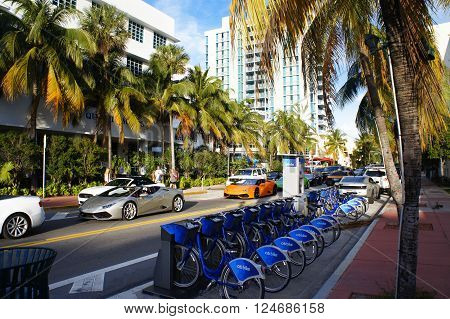MIAMI BEACH, UNITED STATES - FEBRUARY 5: People and cars move down the street near bycicle parking on 5th of February, 2016 in Miami Beach.