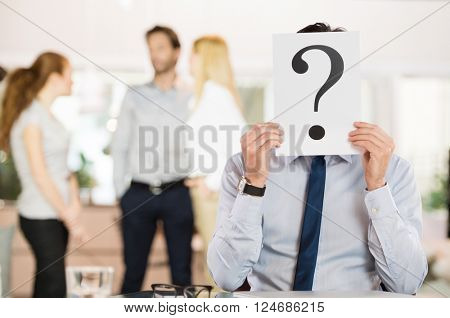 Businessman holding a question mark sign in front of his face. Confused businessman explaining his state of mind about his career. Pensive uncertain businessman holding placard on his face.