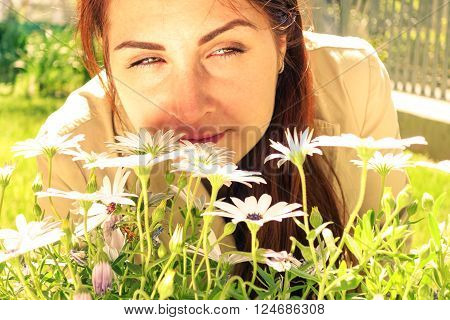 Pensive young woman smelling flowers in the home garden - Girl face with green eyes close up on a spring day - Concept of rebirth with female intense eyes staring -