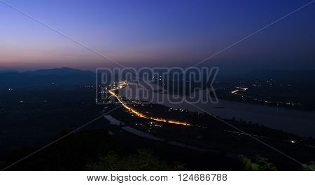 Aerial landscape view of Mekong river with mountain ranges at twilight in Nong Khai Province Thailand. Long exposure shot with street light trails