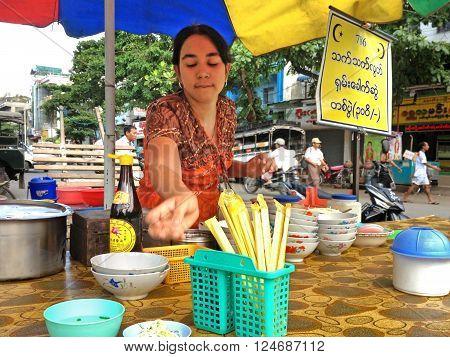 MANDALAY MYANMAR - APRIL 18 2013 : A woman is serving a noodle soup in a noodle shop at Mandalay Myanmar