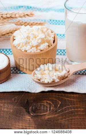 Cottage Cheese, Glass Of Milk, Two Eggs, Wooden Spoon With Cottage Cheese And Wheat Ears Lie On The