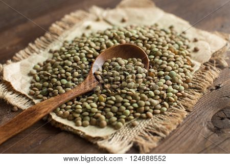 Green lentils with a spoon on a wooden table top view