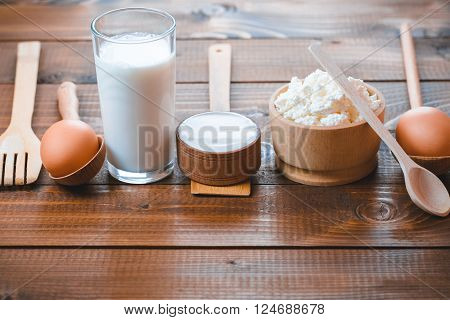 Dairy Products On Wooden Table. Sour Cream, Milk, Cheese, Yogurt And Eggs. Top View With Copy Space