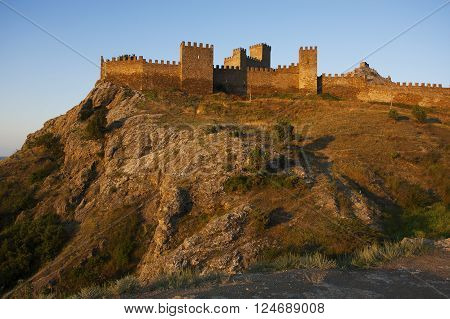 Ancient fortress standing high on a mountain at sunrise