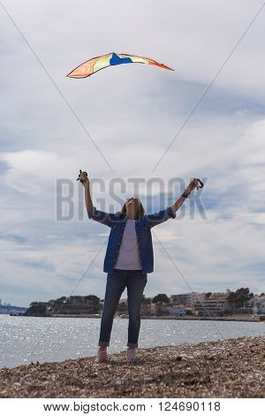 Adult woman on coastline holding colorful flying kite while looking up with outstretched arms