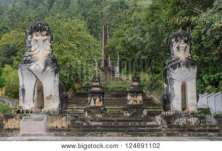 Burmese sculpted lions statue at stairways leading up to the hill at Wat Phra Non in Mae Hong Son, Thailand