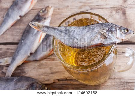 dried fish vobla with beer on the table background