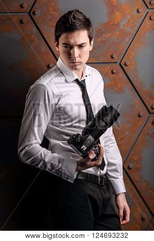 Man photographer in studio with DSLR camera in hand and black tie