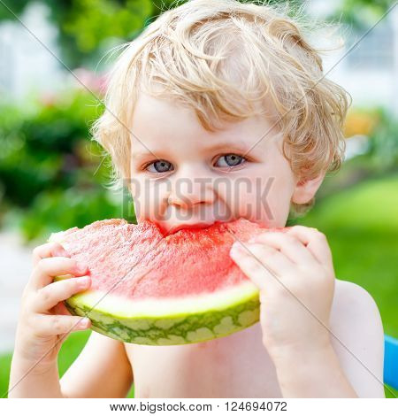 Funny little toddler boy with blond hairs eating watermelon at nursery outdoors. Kid tasting healthy snack. Healthy food for children.