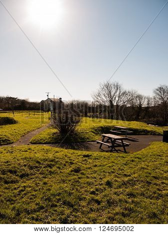A picnic bench area absent of people surrounded by grass.