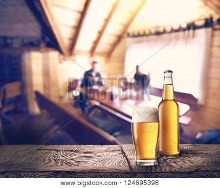 Bottle and glass of beer on table against background of cafe