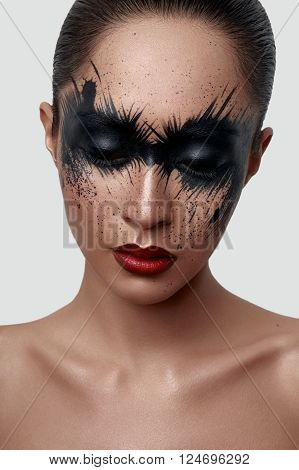 Beauty Fashion Girl with black Paint Splashes on her Face. Creative Face Art Concept for Magazine or Poster
