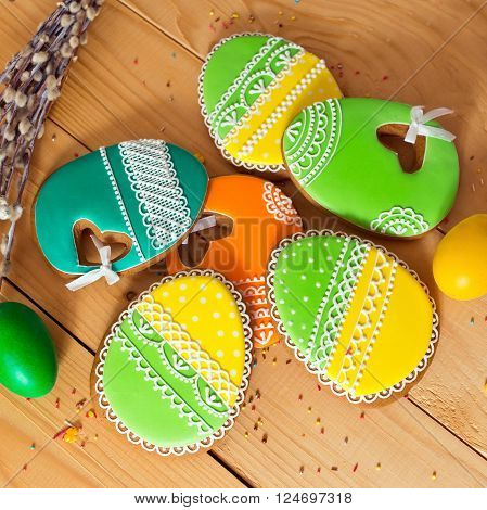 Easter homemade gingerbread cookie, willow and yellow end green eggs on wooden table. Colorful image, top view