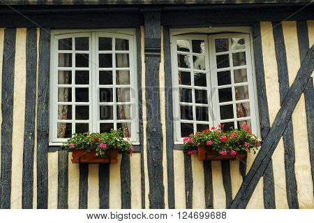 Pont-l'Eveque (Calvados Normandy France): typical old half-timbered house a window with flowers
