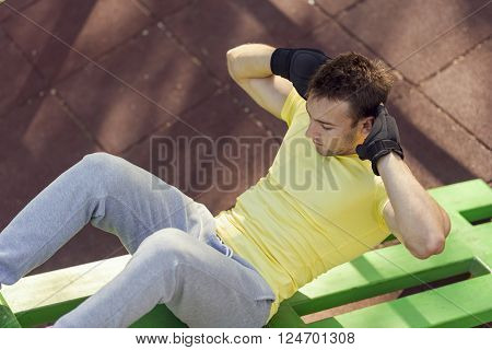 Young sportsman working-out in an outdoor gym doing a series of crunches