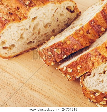 sliced wholegrain bread with oats and nuts, on cutting board