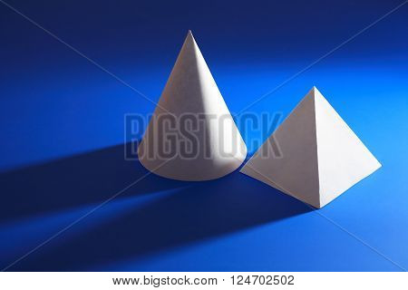 Geometry concept. White paper cone near pyramid on blue background