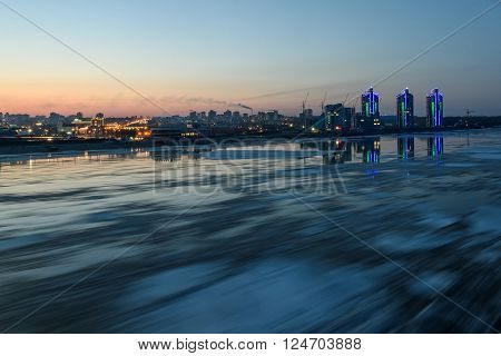 Scenic night view on the breaking of the ice on the river with a fast flowing on the background of city with lights and reflections in water shot on a long exposure