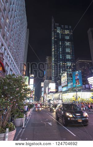 New York City, USA, July 30, 2013:Tourists at Times Square at night, the famous location in New York city, full of people and cars and its neon light signs. ** Note: Visible grain at 100%, best at smaller sizes
