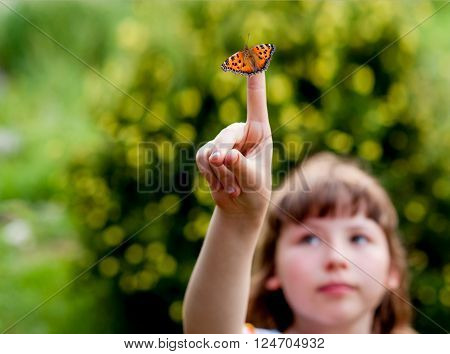 Little girl looks at a butterfly on his finger. Aglais urticae L. ** Note: Visible grain at 100%, best at smaller sizes