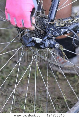 Unrecognizable woman in pink glove fixing dirty bicycle chain in close-up