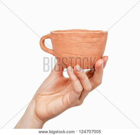 Close view of a clay cup in a woman's hand isolated on white background