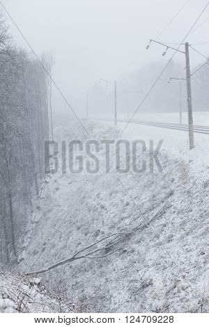 Train tracks in winter heavily snowing. Slope and fallen tree