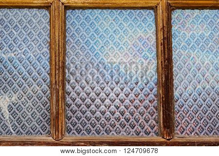 Close up of vintage old window frame with glass panels with pattern