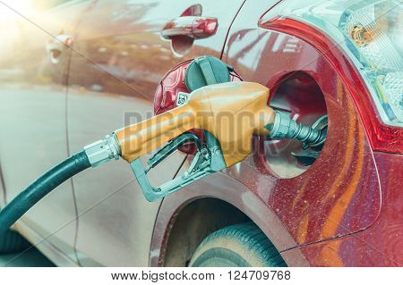 Close up of nozzle car refueling on a petrol station.