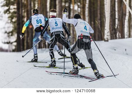 Kyshtym, Russia -  March 26, 2016: group of male skiers going uphill view from back during Championship on cross country skiing