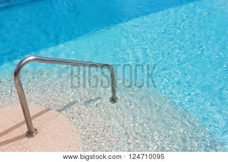 Calm swimming pool steps and handrail. In summer.
