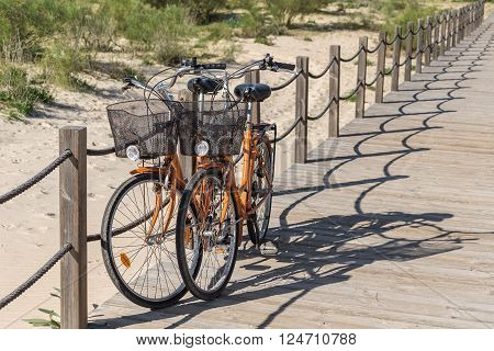 Couple recreational bicycles near the beach. Parked for the carriage of baggage.
