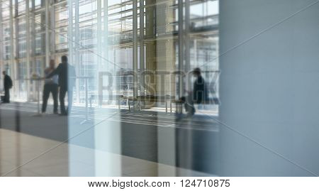 Abstract images of real businesspeople in motion through glass in a busy conference centre
