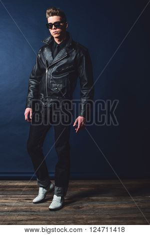 Macho retro 50s fashion man wearing shades and leather jacket.