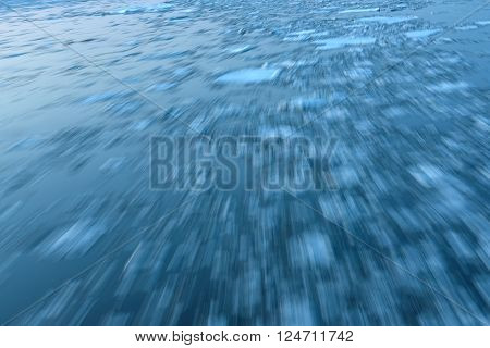 Abstract decorative background of moving ice on the river with fast stream shot on a long exposure